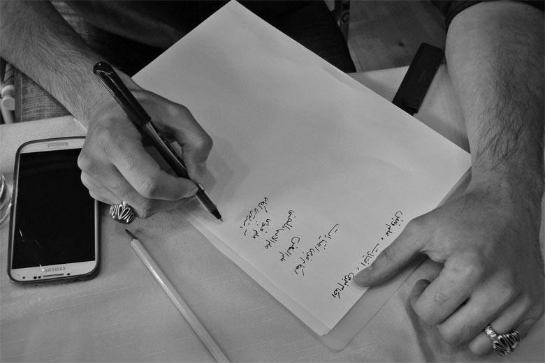 Ahmad Mansoor schreibt während des Gesprächs mit der Autorin die Wörter auf, die der Übersetzer Ahmad nicht verstanden hat.